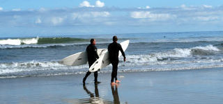 Two surfers about to enter the surf on an Avon NC beach.